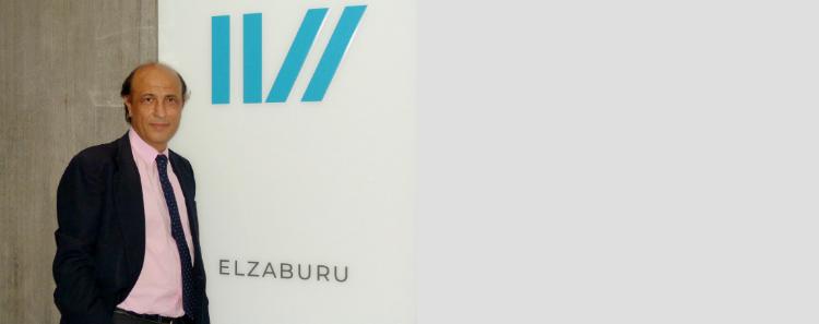 Antonio Tavira junto al nuevo logo de ELZABURU